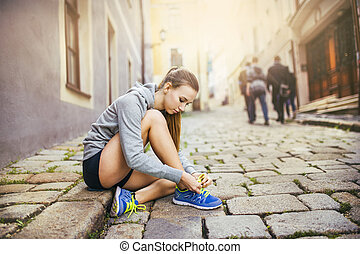 Young female runner tying her shoes - Young female runner is...