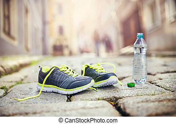 Running shoes and bottle of water left on tiled pavement in...