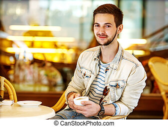 Young fashion man with beard drinking espresso coffee in the...