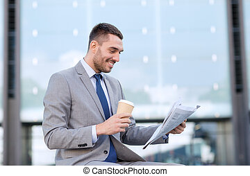 young businessman with coffee and newspaper - business, hot...