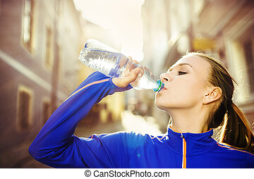Female runner having break - Young female runner is having...