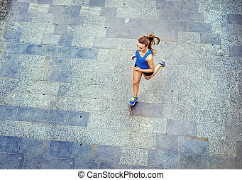 Young woman running in city center - High angle view of...