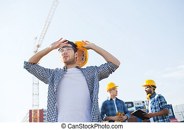 group of builders in hardhats outdoors - business, building,...