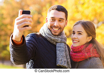 smiling couple with smartphone in autumn park - love,...