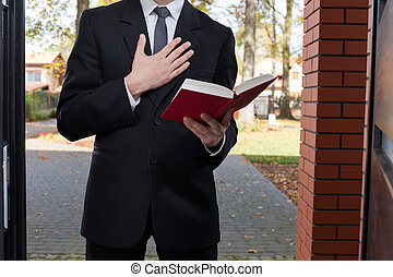 Jehovahs witness standing at the door and holding Bible