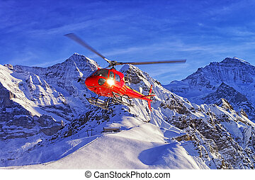 Red helicopter landing at swiss ski resort near Jungfrau...