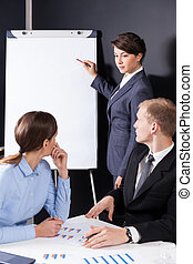 Manager writing on the board during business meeting