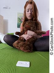 Teenqe girl checks pregnancy test - Worried teenage girl...