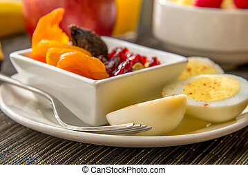 Sliced hard boiled eggs and fruit nutricious breakfast -...