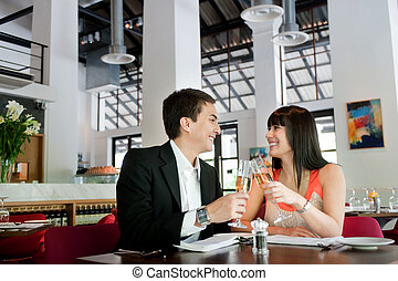 Couple with Wine - An attractive young couple toasting with...