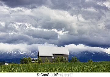 A house in grass field with mountain background