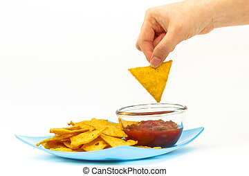 Dipping tortilla chips with salsa sauce in dish on white backgro