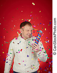 Man with cracker - Joyful man having fun with confetti...