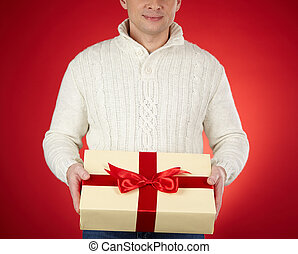 Showing giftbox - Young man in white pullover holding...