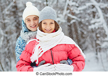Winter romance - Young amorous couple in warm clothes...