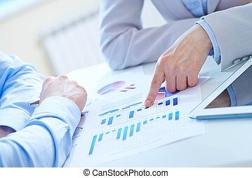 Presentation - Forefinger of businesswoman pointing at chart...