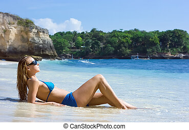 Blonde girl relaxing in water on the beach on Bali island in...