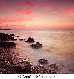 litoral, com, nebuloso, água, em, pôr do sol,