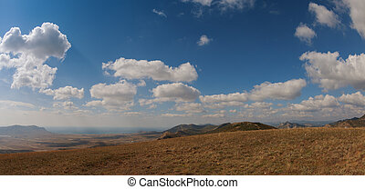 Mountains under the blue sky with clouds
