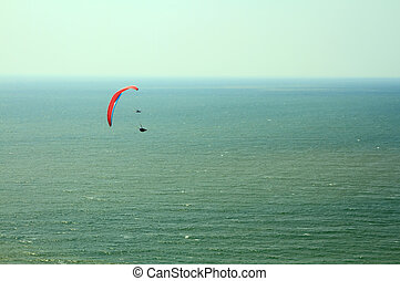 Red paraglider flying in blue sky over the ocean.