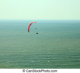 Red paraglider flying in blue sky over the ocean