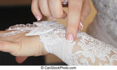 bride straightens glove and holding a finger on the patterns