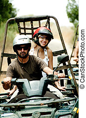 Quad driver in action - Young man drives the quad as female...