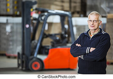 warehouse employee - A warehouse employee is posing in front...