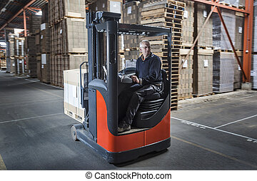 Fork lift operator preparing products for shipment - Fork...