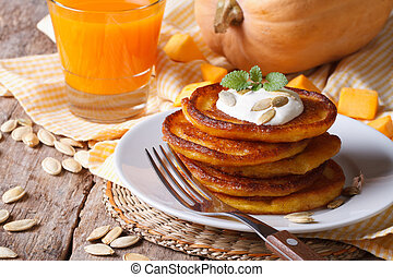 Pumpkin pancakes with sour cream and juice with pulp closeup...