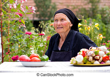 Elderly woman talking at the table - An old woman talking at...