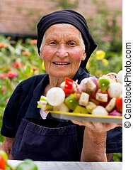 Elderly woman with fresh food - An old woman holding fresh...