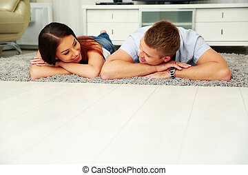 Happy couple relaxing on the floor at home
