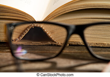 glasses with books - reading glasses with bokks on the table