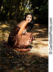 Scared woman in forest sitting on the ground with fashion dress