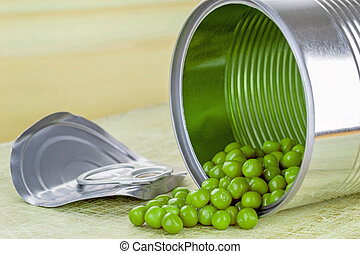 Open Tin of Green Peas - Green peas spilling out of a tin...
