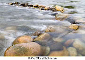 Water flowing over beautiful stones through the France...