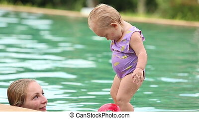 mother and daughter swim in the pool