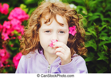 Curly baby with flowers in her hand. Toning photo. Instagram...