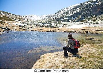squatting woman at the valley - woman hiking at gredos...