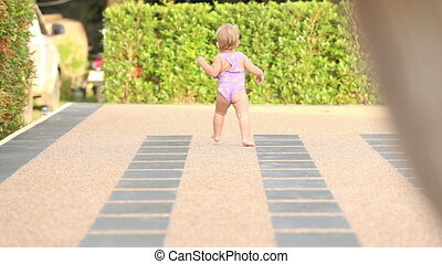one year baby girl runs near the swimming pool