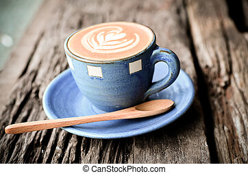 Latte art, Blue coffee cup on wooden background with vintage...