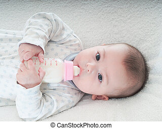 Baby boy drinking milk from the bottle at home - Caucasian...
