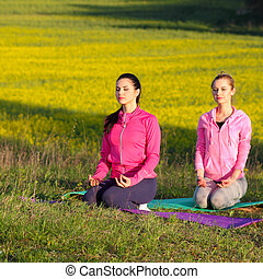 Two women doing yoga outdoors yoga instructor shows poses