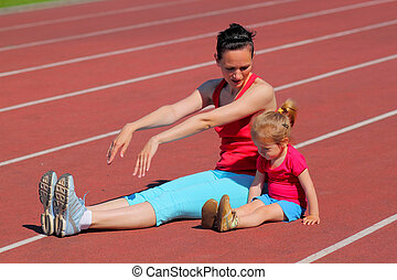 Mother and little daughter are engaged in running in the...