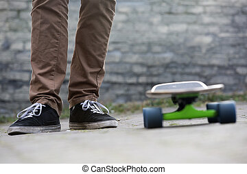 Skateboarder feet and skateboard in urban setting - The two...