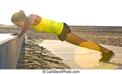 Woman doing Press ups on a beach - Young, pretty looking...