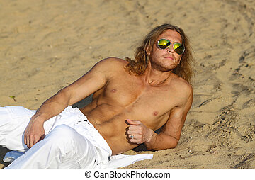 Fitness model man with long hair and wearing sunglasses...