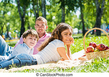 Weekend with family - Happy family of three lying in summer...