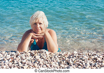 Senior woman lying on the beach - Portraite of senior woman...